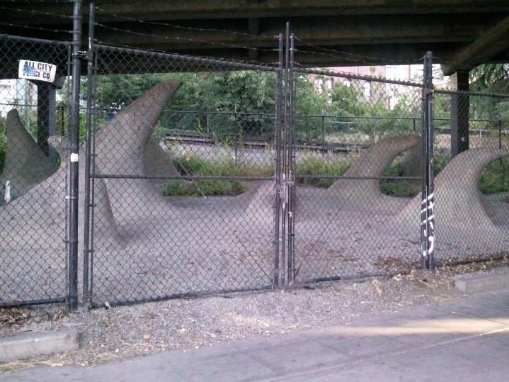Fenced sculptures under a bridge