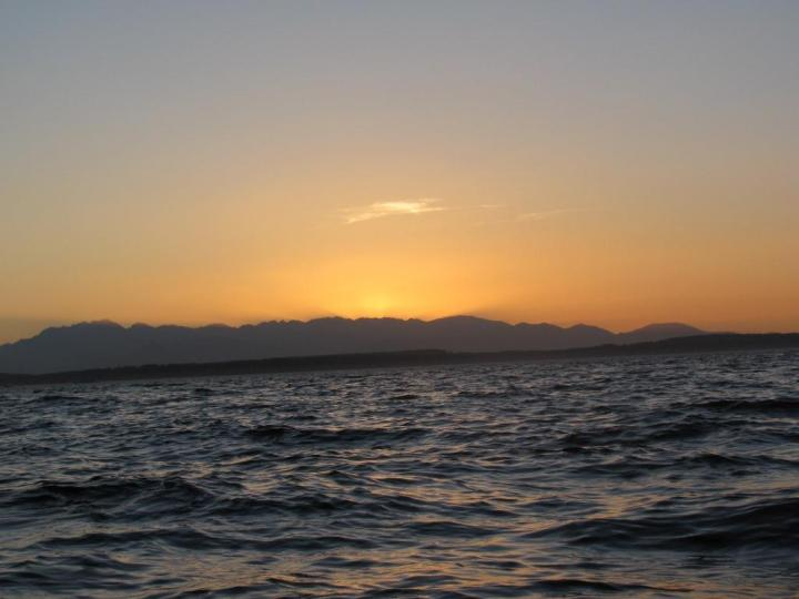 Watching the sun set behind the mountains from the water